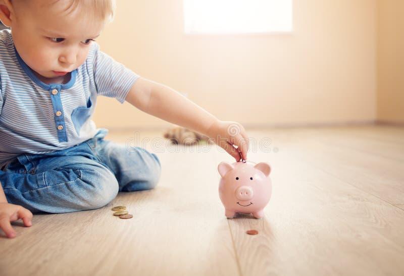 两岁坐地板和放硬币的儿童入piggybank 图库摄影
