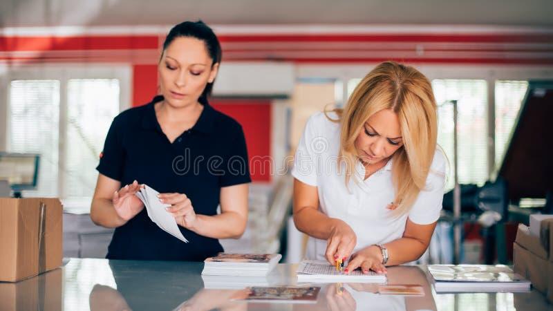 两工作在打印工厂的少妇 免版税库存照片