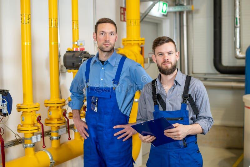 两工作者在工厂设备 图库摄影