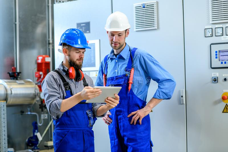 两工作者在工厂设备 库存图片