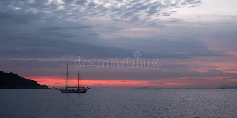 两帆柱在远的距离的帆船在天际在离意大利的海岸的附近那不勒斯海湾的在索伦托附近的在意大利 免版税图库摄影