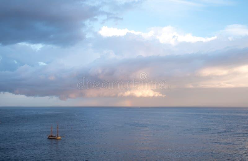 两帆柱在远的距离的帆船那不勒斯海湾在索伦托附近的在意大利 拍摄与在早m的喜怒无常的天空 免版税库存图片