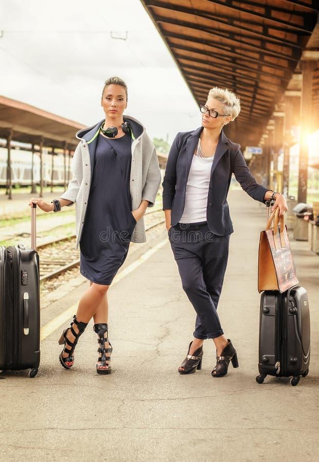两带着摆在火车站的手提箱的端庄的妇女 免版税库存图片