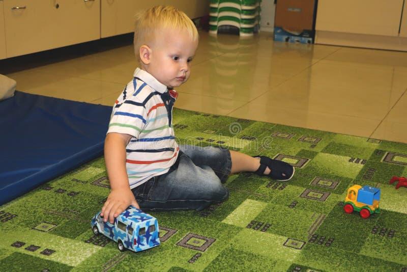两年儿童与汽车的男孩戏剧 幼儿园和幼儿园孩子的,室内操场,生活方式概念教育玩具 免版税图库摄影