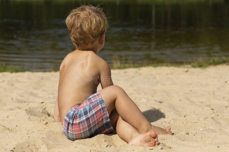 两年坐沙子和享用海滩的男婴,看起来去,后面看法 美丽的概念池假期妇女年轻人 免版税库存图片