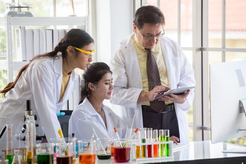 两年轻亚裔妇女研究科学家和准备试管和分析有计算机的老人监督员显微镜 免版税库存照片