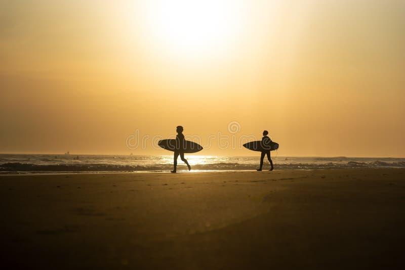 两年轻人剪影有冲浪板的 库存照片