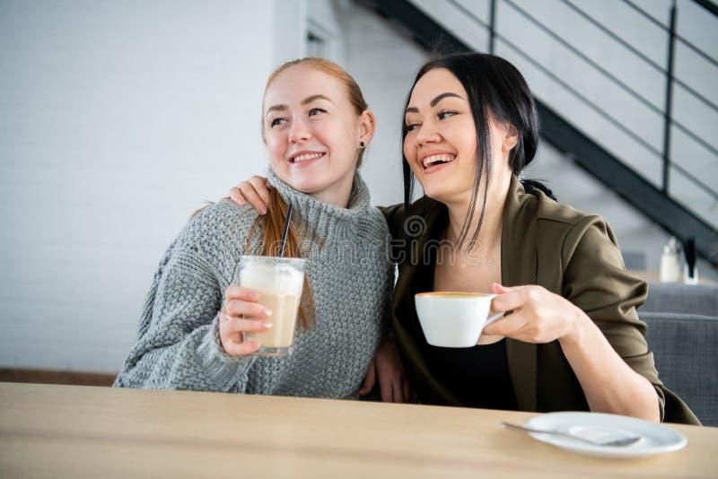 两年轻人和美女见面在热奶咖啡的酒吧和聊天 免版税图库摄影