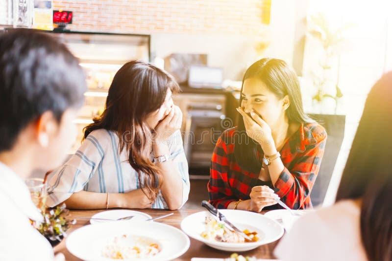两年轻和一起谈话和笑在午餐时间的逗人喜爱的亚裔妇女 免版税库存图片
