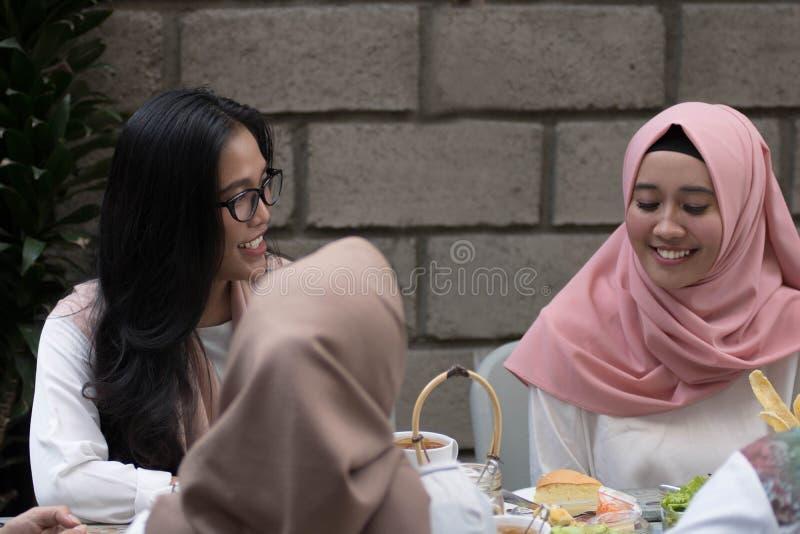 两年轻回教女性有交谈,当享受膳食时 免版税库存照片