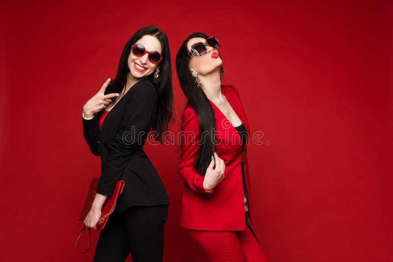 两年轻在太阳镜微笑的摆在的时尚时髦的女性模型被隔绝在红色演播室 库存照片