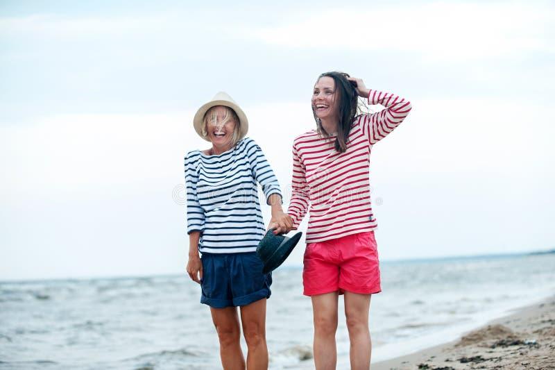 两年轻女人一起获得乐趣在风雨如磐的海边 免版税库存图片