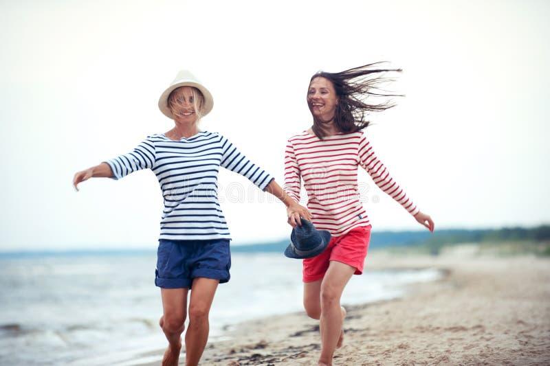 两年轻女人一起获得乐趣在风雨如磐的海边 图库摄影