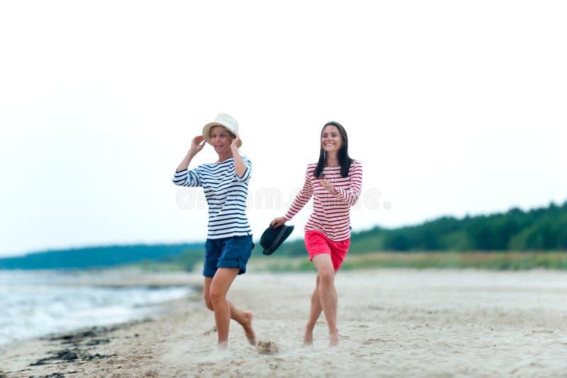 两年轻女人一起获得乐趣在风雨如磐的海边 库存照片