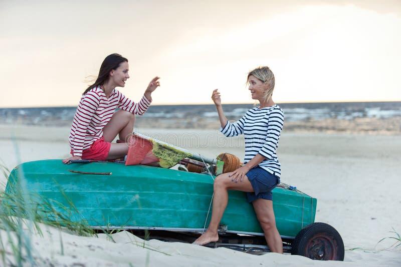 两年轻女人有交谈在夏天有风海岸 图库摄影