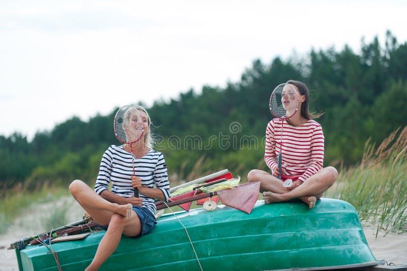 两年轻女人有交谈在夏天有风海岸 库存图片