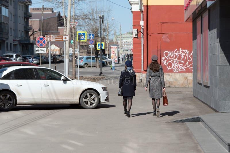 两年轻女人,时兴地打扮,步行沿着向下通过一辆停放的汽车的一条城市街道在一春天好日子 免版税库存照片