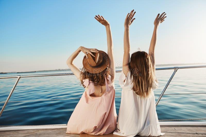 两年轻女性室外后面射击豪华假期,挥动在海边,当坐游艇时 最好的朋友是 免版税库存照片