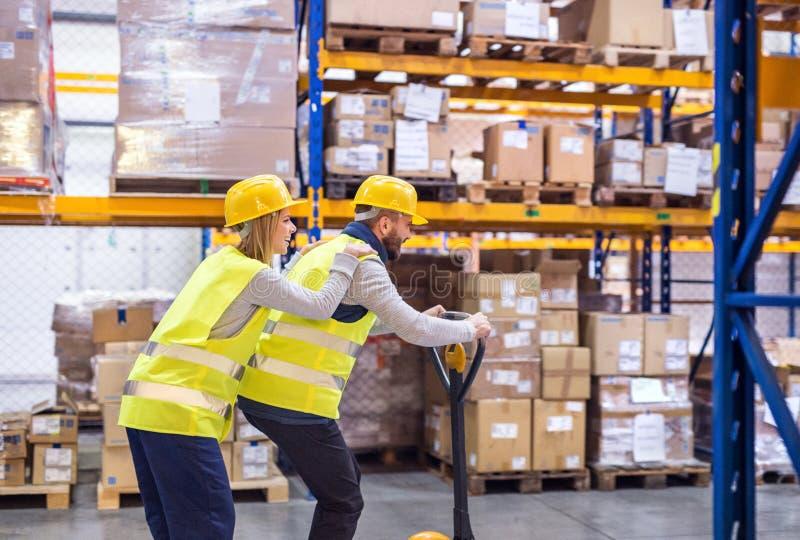 两年轻工人在仓库里 免版税库存图片
