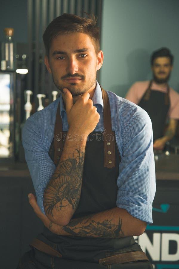 两年轻时髦的barista在咖啡馆摆在 免版税库存照片