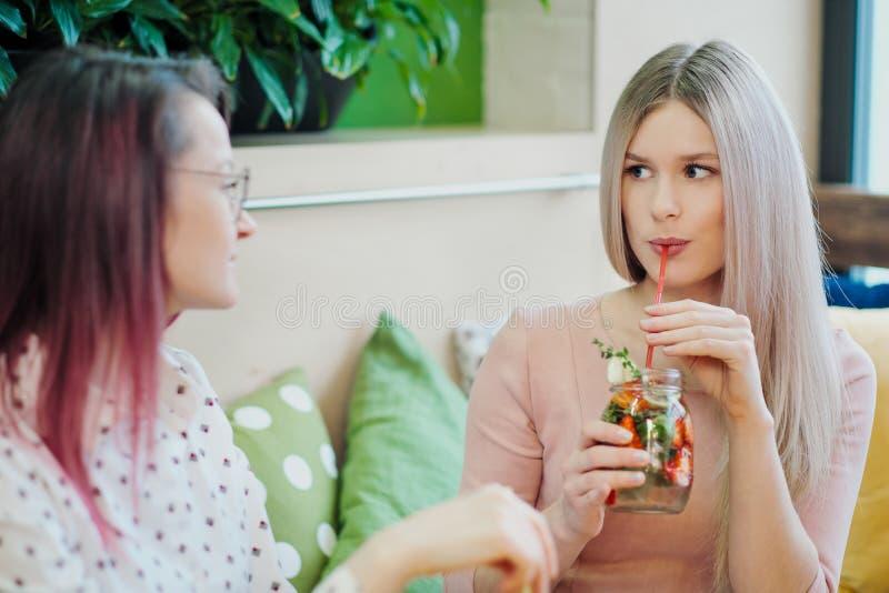 两年轻美女、一个金发碧眼的女人一件桃红色礼服的和一个浅黑肤色的男人有被染的头发的,坐在咖啡馆桌,饮料柠檬水上 库存图片