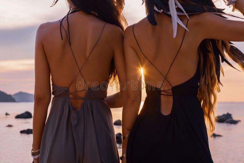 两年轻美女剪影获得在海滩的乐趣在日落 免版税库存照片