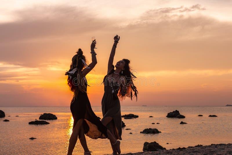 两年轻美女剪影获得在海滩的乐趣在日落 库存图片
