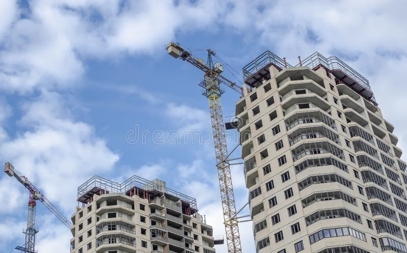 两座毗邻高层建筑物建设中反对一明亮的天空蔚蓝 免版税库存图片