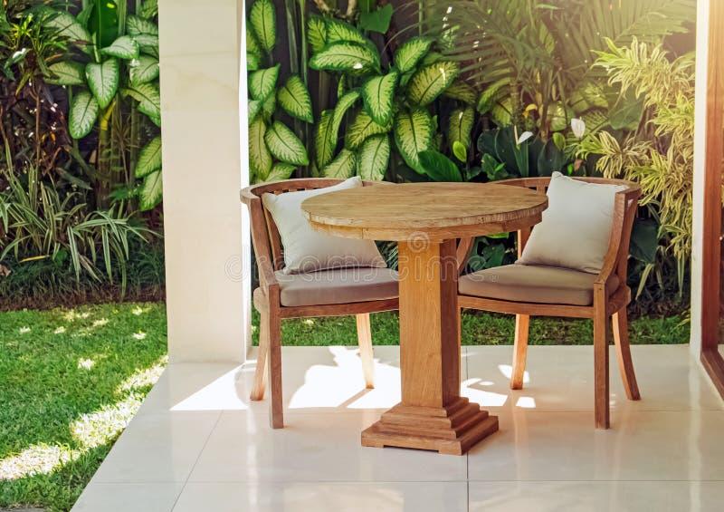 两张木椅子和桌在充分庭院里绿色热带植物 库存图片