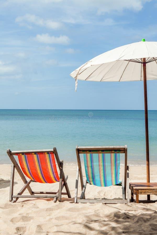 两张海滩躺椅在海滩的伞下 库存图片