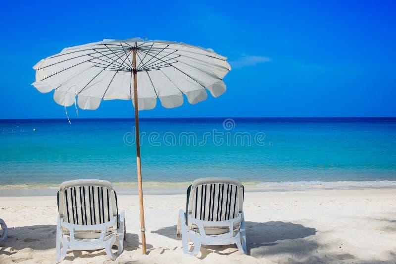 两张白色海滩睡椅和白色umbella在白色沙子靠岸 免版税库存照片