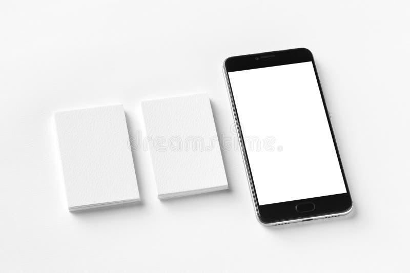两张空白的垂直的名片和黑手机大模型在白色织地不很细纸 图库摄影
