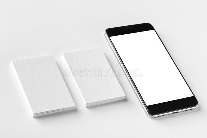 两张空白的垂直的名片和黑手机大模型  免版税库存照片