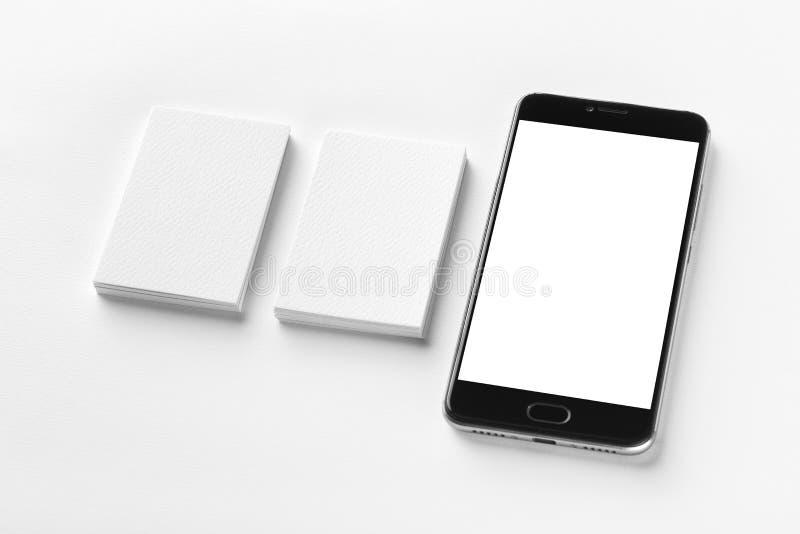 两张空白的垂直的名片和黑手机大模型  库存照片