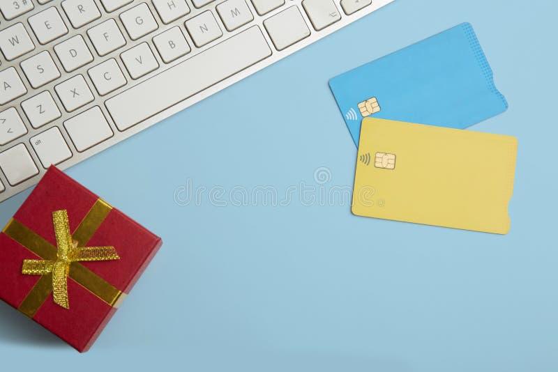两张空白的颜色信用卡大模型,在空的蓝色书桌背景的礼物盒 企业消息的大模型背景 免版税库存图片