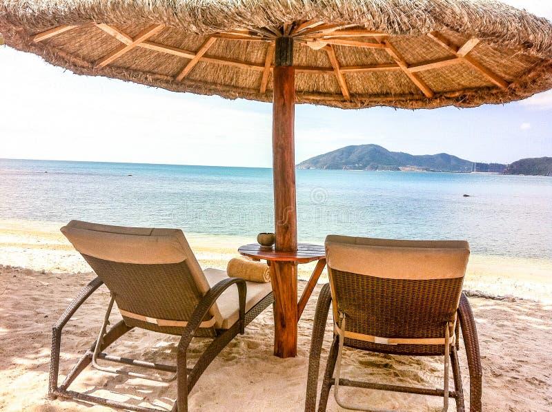 两张躺椅和一个海滩帐篷在海滩 库存照片