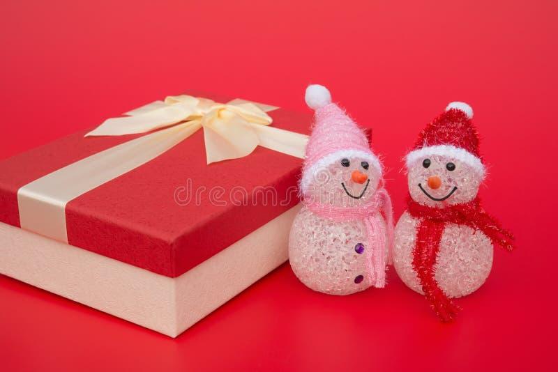 两微笑的玩具圣诞节雪人和一个当前箱子在红色 免版税库存照片