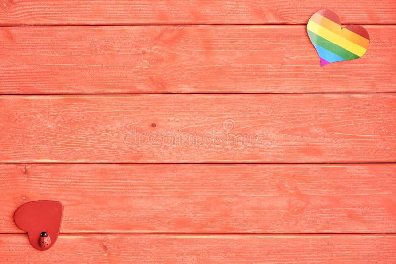 两心脏在居住的珊瑚的一种木背景颜色说谎 与LGBT社区和另一红色彩虹的一心脏  库存图片