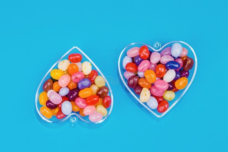 两心脏用在蓝色背景的糖果 免版税库存图片