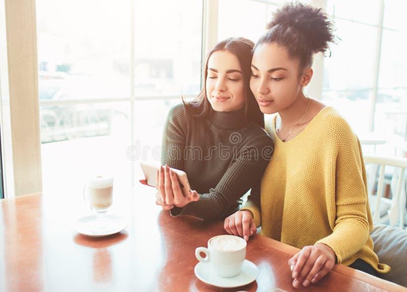 两快乐和美丽的女孩在桌附近一起坐并且观看某事在电话 他们看 库存图片
