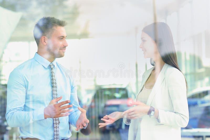 两快乐的微笑的年轻买卖人谈话在办公室 库存图片