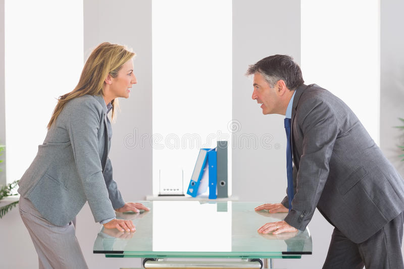 两恼怒的买卖人争论在书桌的每边 库存图片