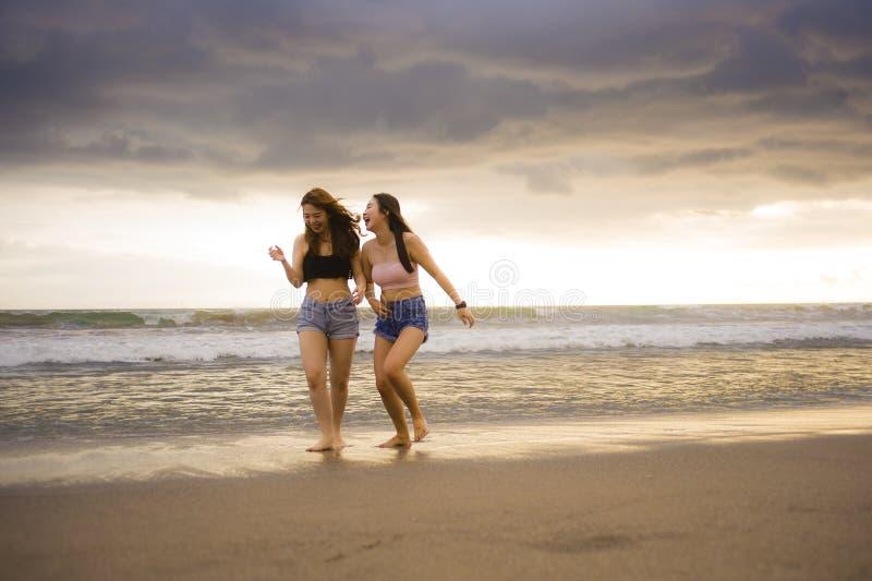 两愉快和获得可爱的年轻亚裔中国妇女的女朋友或者的姐妹走在海滩笑的和谈的bea的乐趣 库存图片