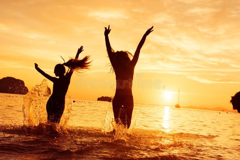 两愉快的女孩奔跑向日落海 免版税库存图片