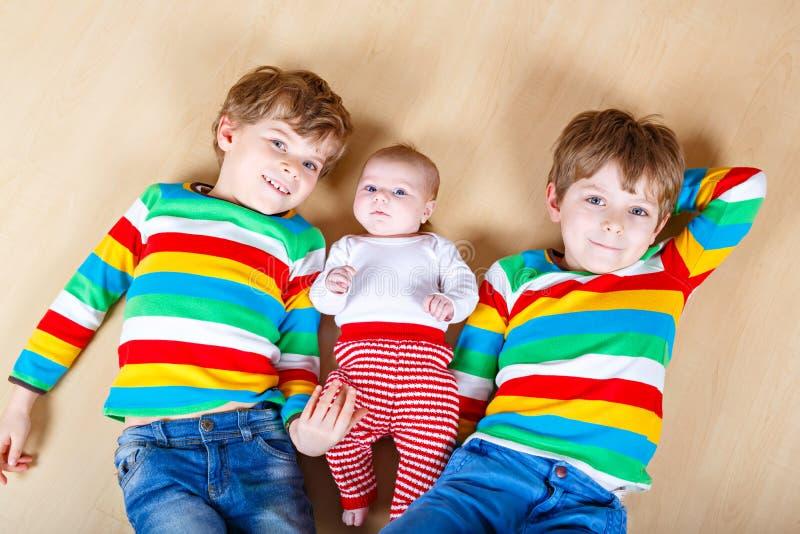 两愉快的小的幼儿园哄骗有新出生的女婴的,逗人喜爱的姐妹男孩 兄弟姐妹,孪生孩子和婴孩使用 免版税库存照片