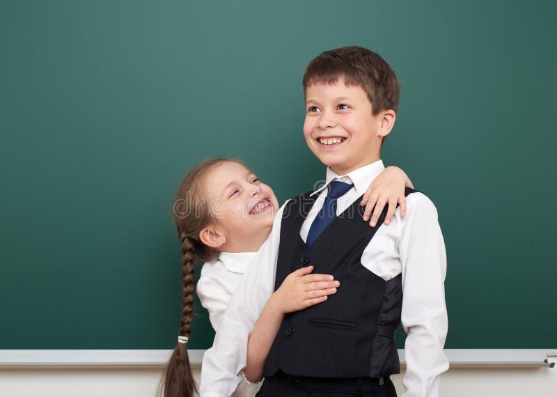 两所学校学生摆在干净的黑板的,做鬼脸和情感,在一套黑衣服,教育概念,演播室phot穿戴了 免版税库存图片