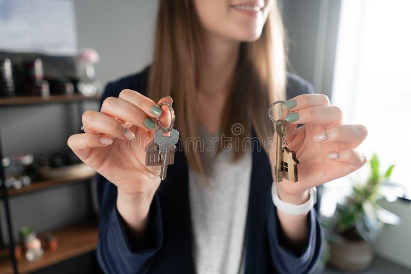 两把房子钥匙在妇女手上 年轻俏丽的妇女微笑 现代轻的大厅内部 不动产,抵押权,移动 免版税库存照片