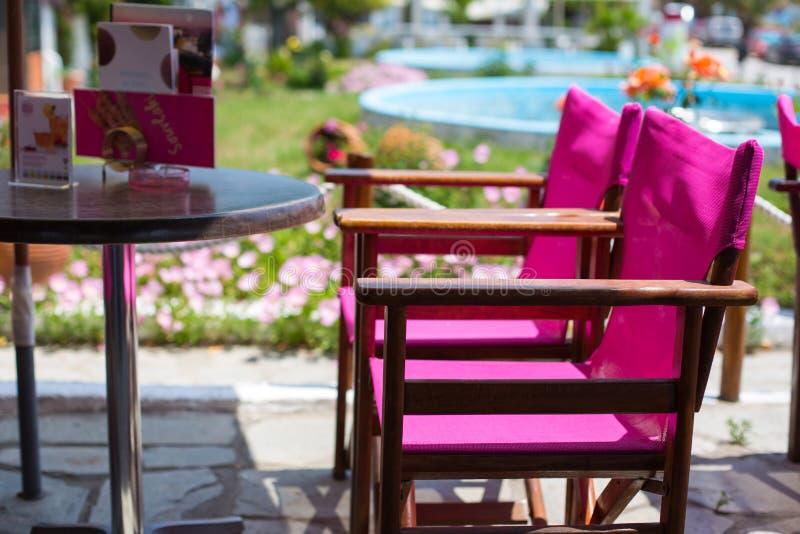 两把明亮的紫色在咖啡馆的椅子连续和桌 免版税库存照片
