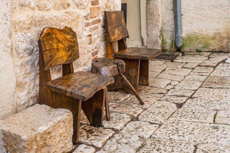 两把椅子和一张桌在城市街道的石路面 手工制造从老木头 古色古香称呼 免版税库存照片