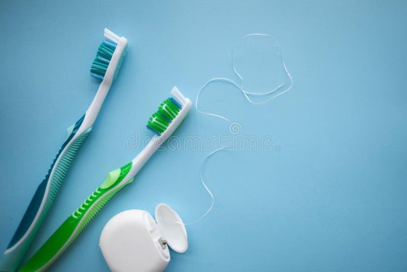 两把牙刷和牙线在蓝色背景 库存图片